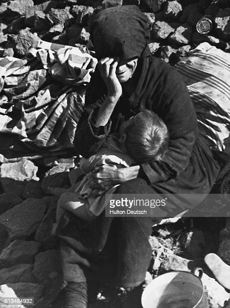 A Civil War refugee from Malaga sits despairingly amidst rubble with her child as she is forced to join others in making her way to Barcelona Valence...