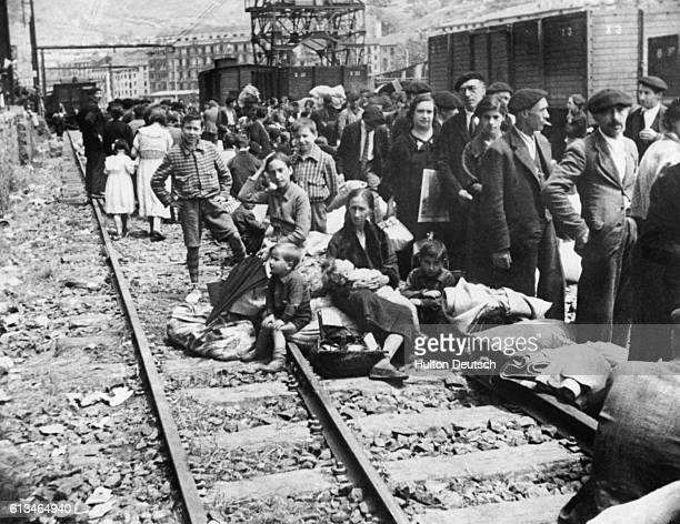 Civil War refugees seen at Bilbao Station returning to the city after it was taken by Franco's nationalist troops