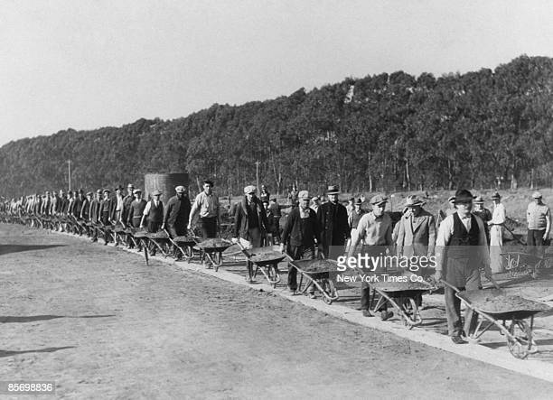 Civil Works Administration workers on their way to fill a gully with wheelbarrows of earth during the construction of the Lake Merced Parkway...