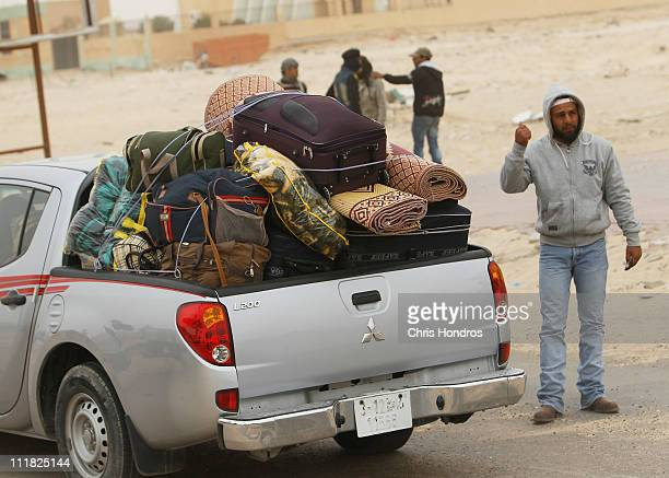 Civilan truck packed with bags is directed down a highway during a hasty withdrawal April 7, 2011 in Ajdabiyah, Libya. A NATO air strike is thought...
