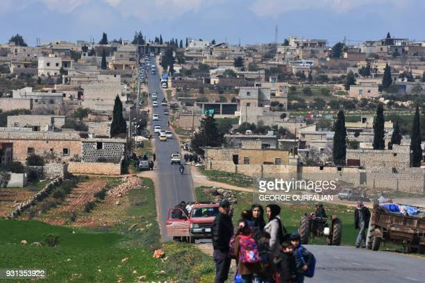 TOPSHOT Civilans fleeing Afrin after Turkey said its army and allied rebels surrounded the Kurdish city in northern Syria pass through azZiyarah an...