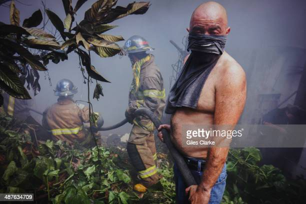 A civilian and several volunteer firefighters bring a hose to put out a fire erupting in a landfill community January 18 2014 in Guatemala City...