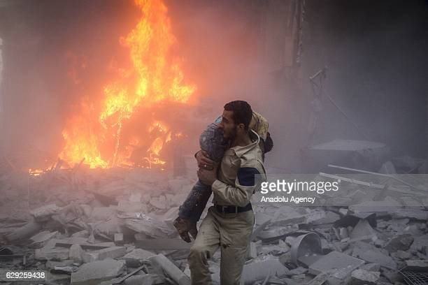 A civilian carries the attack victim Assad forces hit residential areas in Ansari neighborhood of Aleppo Syria on July 31 2016 Several casualties...