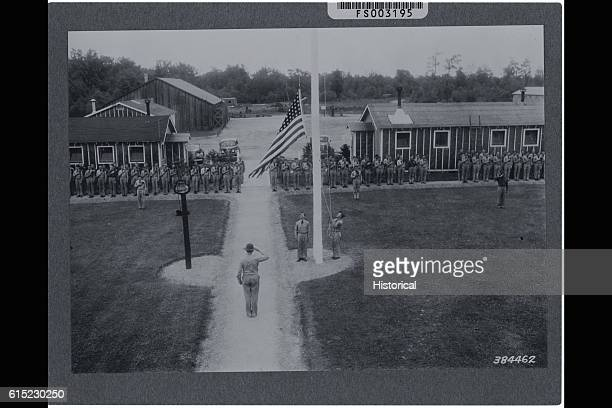 Civilian Conservation Corps personnel at a CCC retreat stand at attention, saluting the American flag as it is raised over the grounds of their camp...