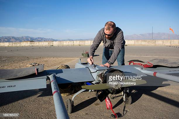 A civilian contractor checks a US Army 14' Shadow surveillance drone before it's launched at Forward Operating Base Shank May 8 2013 in Logar...