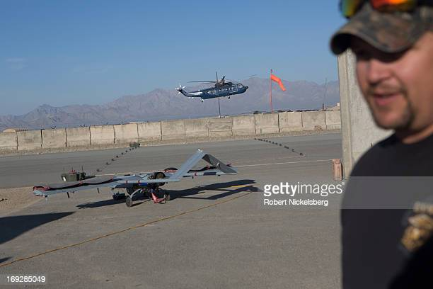 A civilian contractor stands near a US Army 14' Shadow surveillance drone before it's launched at Forward Operating Base Shank May 8 2013 in Logar...