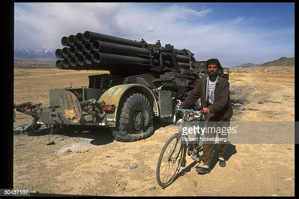 Civilian cyclist by governmenttaken multiple rocket launcher once in arsenal of rival mujahedin Hekmatyar wrecked by another civil war faction