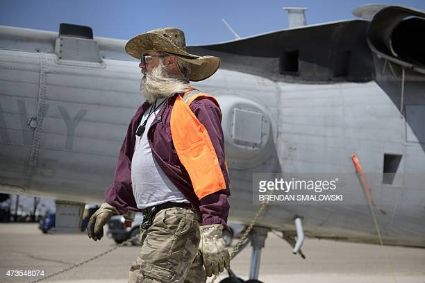 A civilian employee of the Aerospace Maintenance and Regeneration Group walks past a Navy helicopter being placed into storage at the Aerospace...