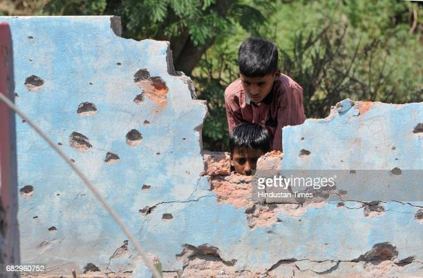 A civilian inspects a damaged house by mortar shells allegedly fired from the Pakistan side of the border at Jhanghar village in Nowshera on May 14...