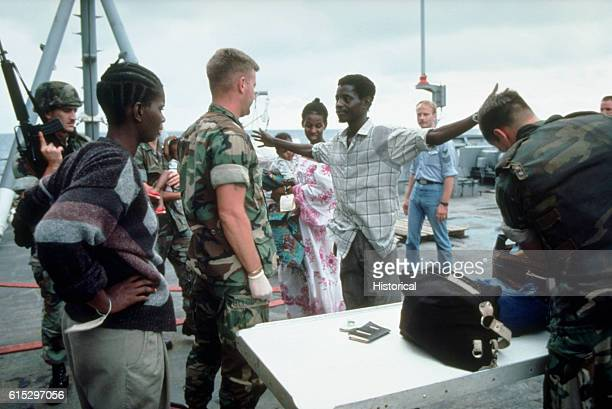 A civilian lifts his arms to be searched by a Marine while being processed aboard the tank landing ship USS Barnstable County during Operation Sharp...