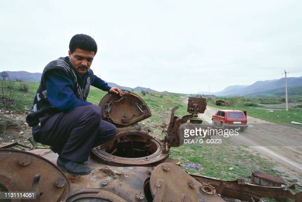 Civilian on a tank used during the Nagorno-Karabakh war and abandoned on the side of a road, Azerbaijan, 20th century.