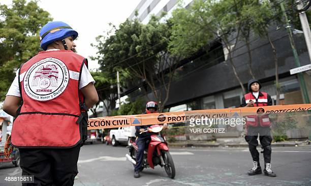 Civilian Protection member close an area where firefighters work to demolish a damaged wall after a strong earthquake in Mexico City on May 8 2014 A...