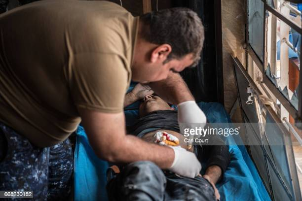 Civilian receives treatment at a field clinic after being shot by an Islamic State sniper in west Mosul on April 13, 2017 in Mosul, Iraq. As the...