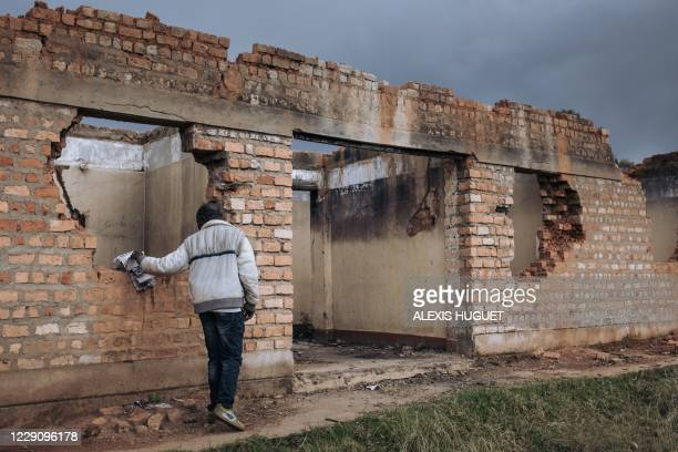 Civilian staff member of the United Nations Organization Stabilization Mission in the Democratic Republic of the Congo inspects the ruins of the...