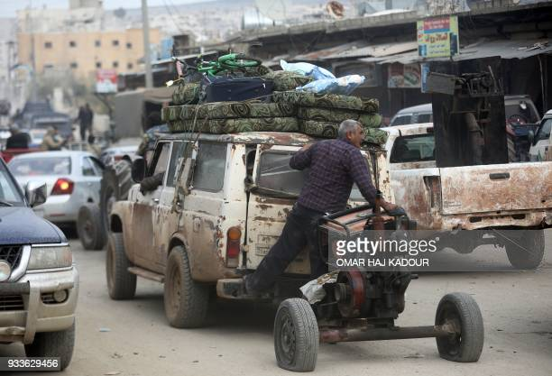 TOPSHOT A civilian stands on the back of a vehicle carrying belongings as they flee the city of Afrin in northern Syria on March 18 after Turkish...
