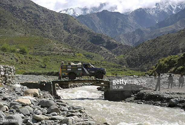 Civilian truck drives over a makeshift bridge outside Naray town, in Afghanistan's eastern Kunar province on April 9, 2009. US President Barack...