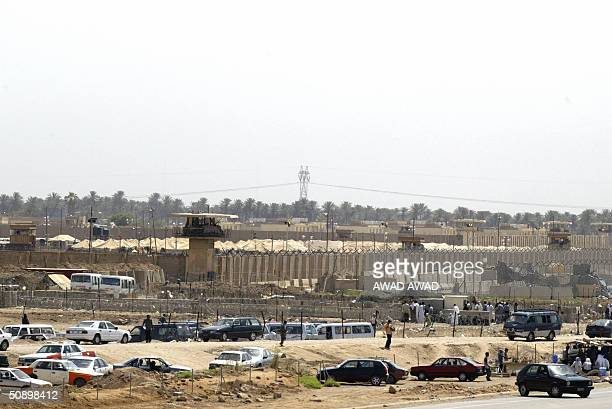 Civilian vehicles are seen parked outside the Abu Ghraib prison west of Baghdad 26 May 2004 as Iraqis gather outside waiting for news of their jailed...