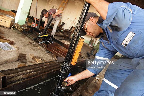 Civilian volunteers rinse old machine gun parts in oil to clean of years of rust and dirt before sending them to the front lines where their fellow...