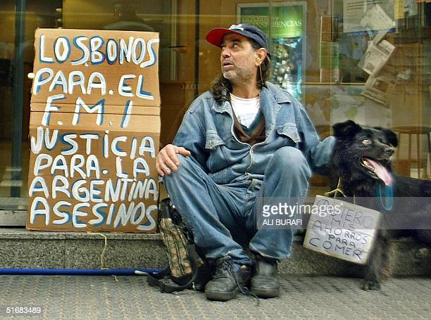 A civilian with his dog claims the return of his depostis from the Banco Nacion Argentina in Buenos Aires 19 July 2002 AFP PHOTO/Ali BURAFI