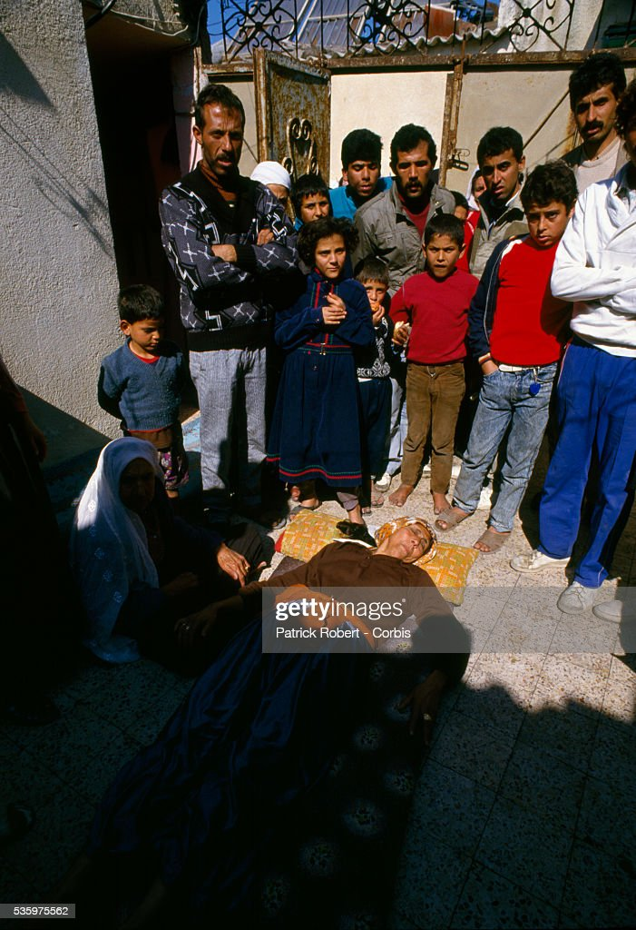 A civilian woman lies wounded on the ground, surrounded by relatives. She was one of the victims of violence after rebel Israeli and Palestinian fighters protested in the occupied territory of Gaza during the first Intifada.
