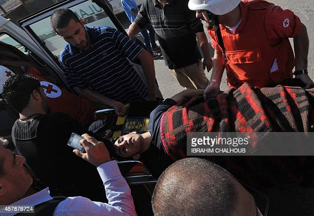Civilians and members of the Lebanese Red Cross evacuate the body of one of the two young Sunni men who were found dead in the Abu Ali river on...