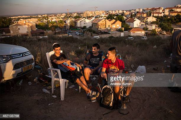 Civilians and members of the media wait to see Israeli attacks inside Gaza from the top of a hill on the sixth day of Israel's operation 'Protective...