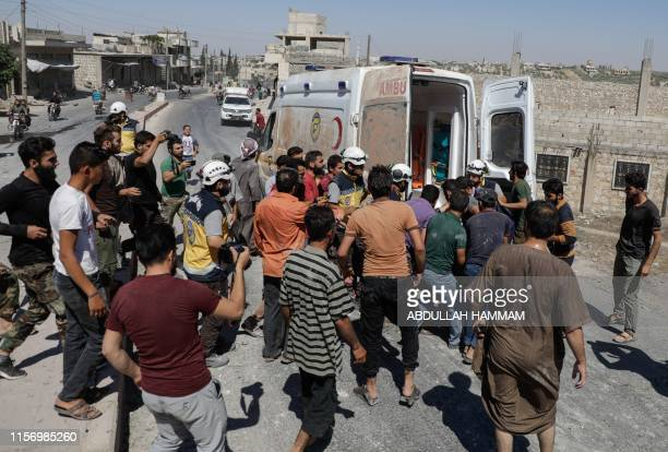 Civilians and members of the Syrian Civil Defence also known as the White Helmets carry the body of a man killed following a reported airstrike by...