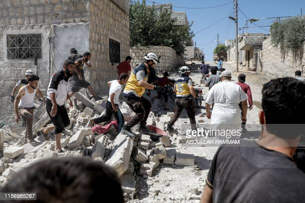 Civilians and members of the Syrian Civil Defence also known as the White Helmets search for bodies or survivors in a collapsed building following a...