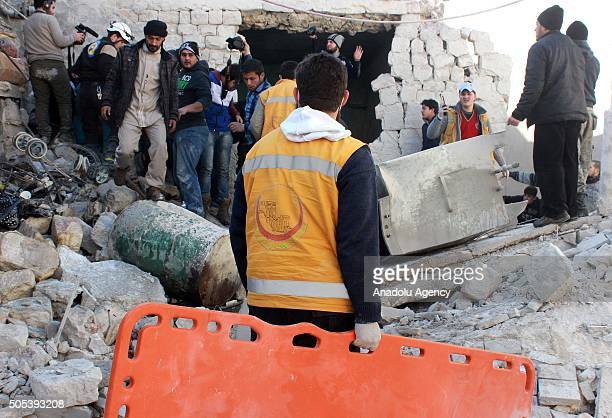 Civilians and rescue workers inscpect rubbles of damaged buildings to rescue victims after Russian airstrikes hit residential areas in Mughair...