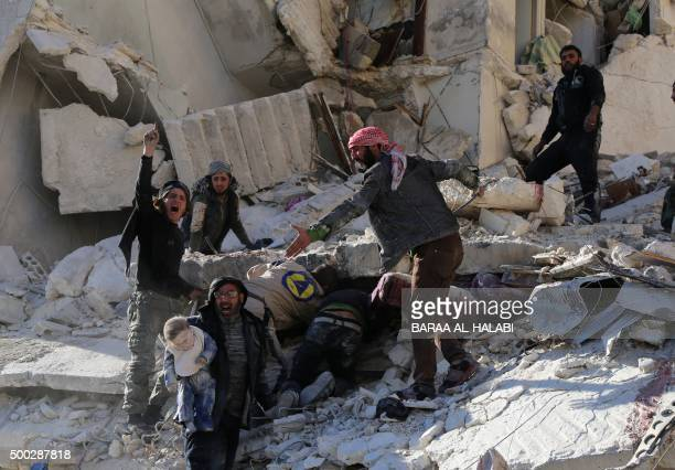 TOPSHOT Civilians and rescue workers remove a toddler and search for other victims amid the rubble of a building following a reported air strike by...