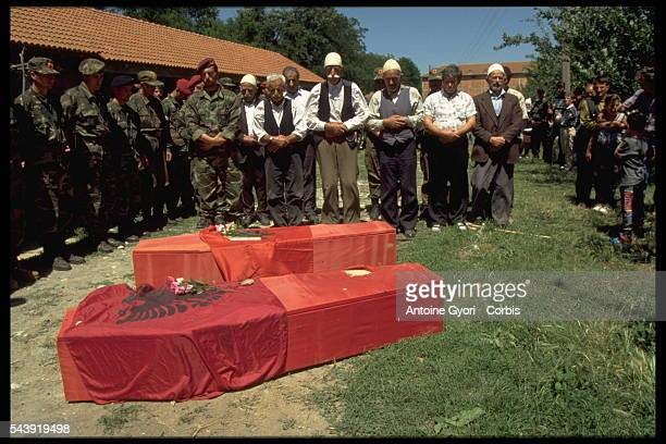 Civilians and soldiers in the Kosovo Liberation Army attend a memorial service in Rogova Kosovo for KLA members who were killed during the...