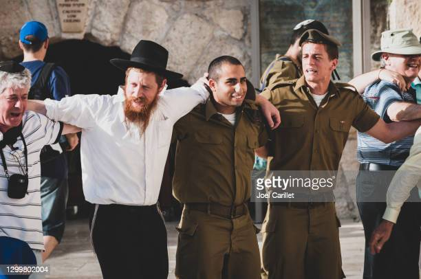civilians and soldiers linking arms at the western wall in jerusalem - israeli military stock pictures, royalty-free photos & images