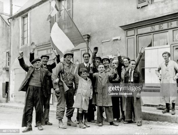 Civilians and two U.S. Soldiers are waving the French flag in front of a store. June 1944. The GIs may belong to the 16th Infantry Regiment 1st...