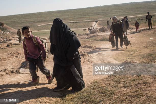 Civilians arrive at an SDF position on the outskirts of Bagouz after walking hours to flee fighting on February 12, 2019 in Bagouz, Syria. Civilian...