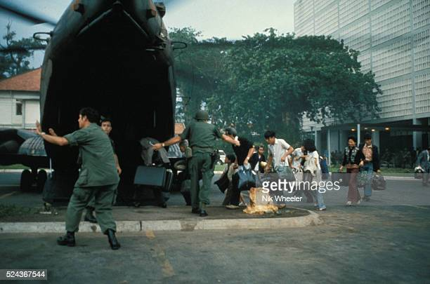 US civilians board helicopter inside the American Embassy compound in Saigon to escape advancing North Vietnamese about to capture Saigon The...