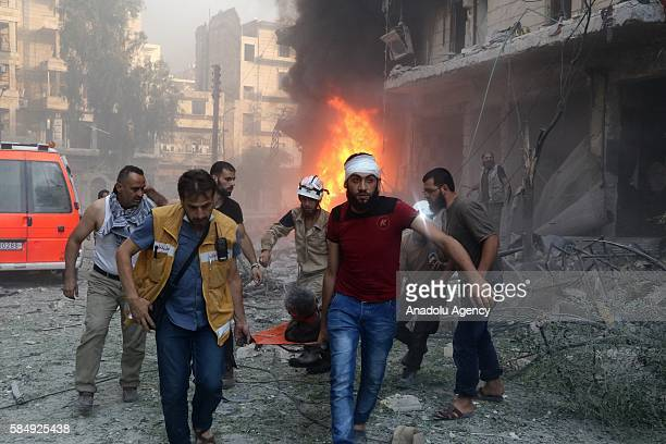 Civilians carry an attack victim after Assad forces hit residential areas in Ansari neighborhood of Aleppo Syria on July 31 2016 Several casualties...