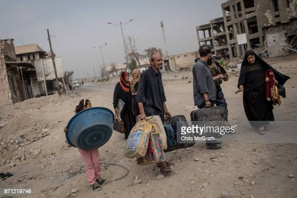 Civilians carry their belongings on a destroyed street in an outer neighborhood of the Old City in West Mosul on November 6, 2017 in Mosul, Iraq....