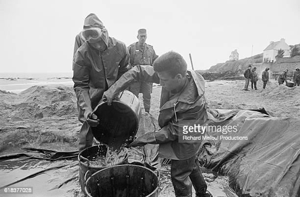 Civilians clean-up one of the beaches in Britanny three months after the Amoco-Cadiz disaster. The supertanker Amoco-Cadiz ran aground off the coast...