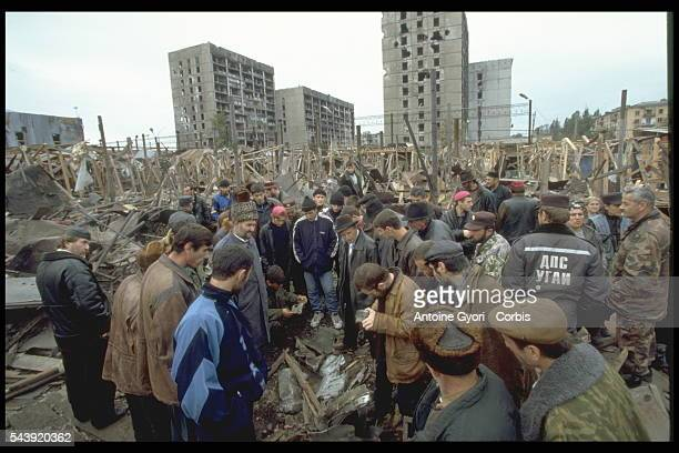 Civilians come back to the main Grozny market after its destruction by a Russian missile the day before