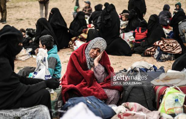 TOPSHOT Civilians evacuated from the Islamic State group's embattled holdout of Baghouz sit at a screening area held by the USbacked Syrian...