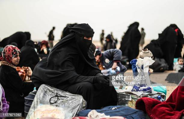 Civilians evacuated from the Islamic State group's embattled holdout of Baghouz sit at a screening area held by the USbacked Syrian Democratic Forces...