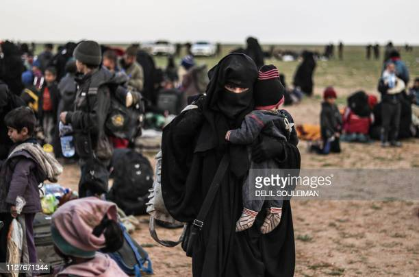 Civilians evacuated from the Islamic State group's embattled holdout of Baghouz wait at a screening area held by the USbacked Syrian Democratic...