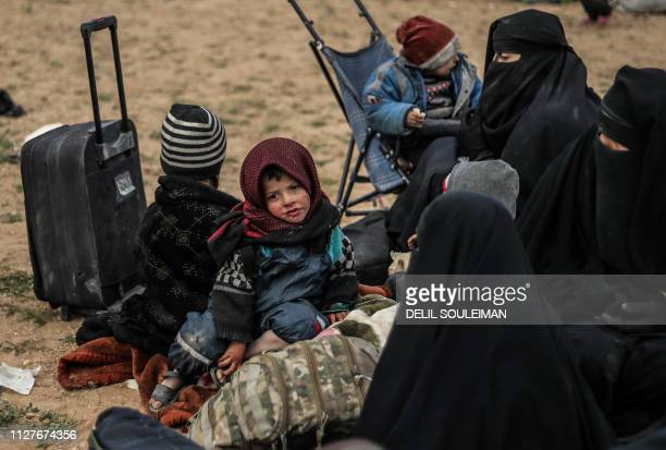 TOPSHOT Civilians evacuated from the Islamic State group's embattled holdout of Baghouz wait at a screening area held by the USbacked Syrian...