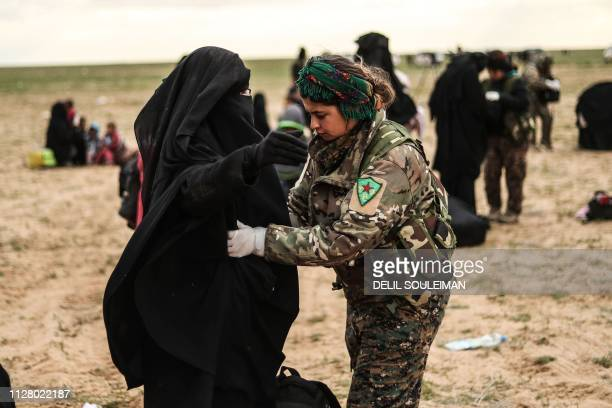Civilians evacuated from the Islamic State group's embattled holdout of Baghouz are searched by the USbacked Kurdishled Syrian Democratic Forces at a...