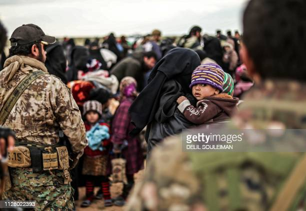 TOPSHOT Civilians evacuated from the Islamic State group's embattled holdout of Baghouz wait at a screening area held by the USbacked Kurdishled...