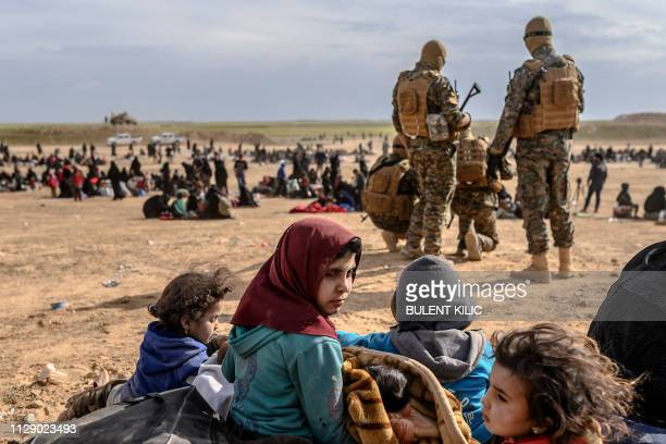 Civilians evacuated from the Islamic State group's embattled holdout of Baghouz wait at a screening area held by the US-backed Kurdish-led Syrian...