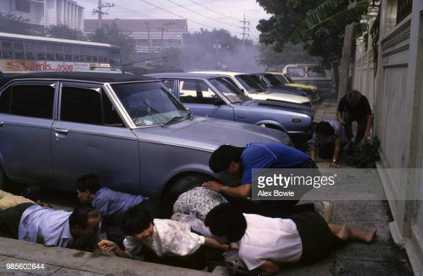 Civilians flee rebel tank and machine-gun fire aimed at a Thai government radio station during a coup attempt, Bangkok, 9th September 1985.