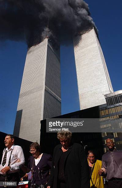 Civilians flee the area as a tower of the World Trade Center collapses September 11, 2001 in New York City after two airplanes slammed into the twin...