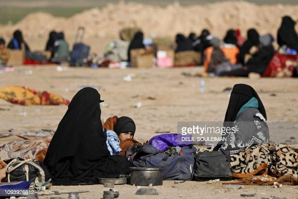 Civilians fleeing fighting between Syrian Democratic Forces and Islamic State jihadists in the frontline Syrian village of Baghuz await to be...