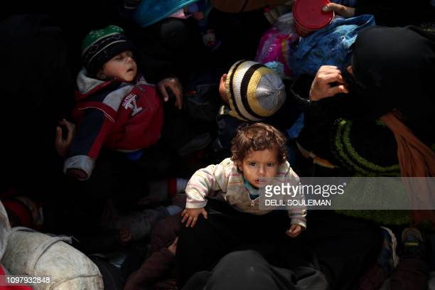 TOPSHOT Civilians fleeing the battered Islamic Stateheld holdout of Baghouz in the eastern Syrian province of Deir Ezzor sit in the back of a truck...